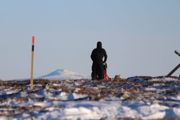 A musher goes over a rocky summit