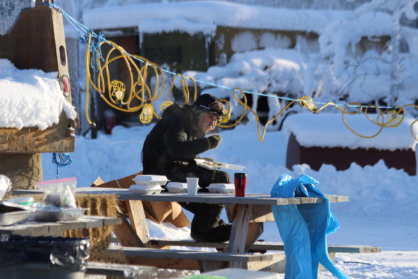 A man in a black snow outfit eats at a wooden picnic bench
