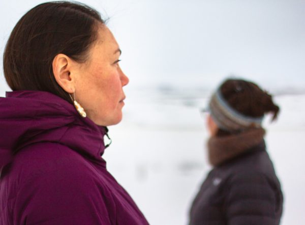 A woman in a purple jacket stares into the distance