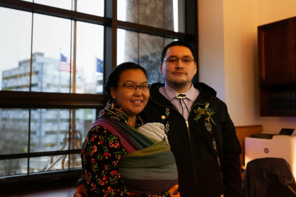 An Alaska Native woman with a baby sling aroundd her stands next to a man in a bolo tie