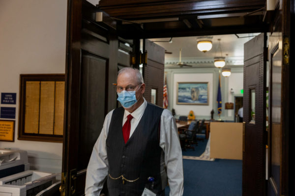 A man in a vest and a red tie walks through a hallway