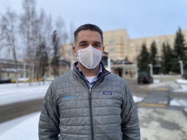 A man stands outside in a jacket and face mask.