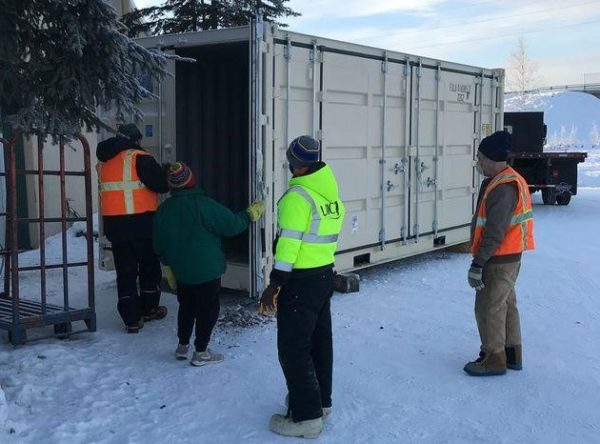 A crew of workers stand around a shipping container