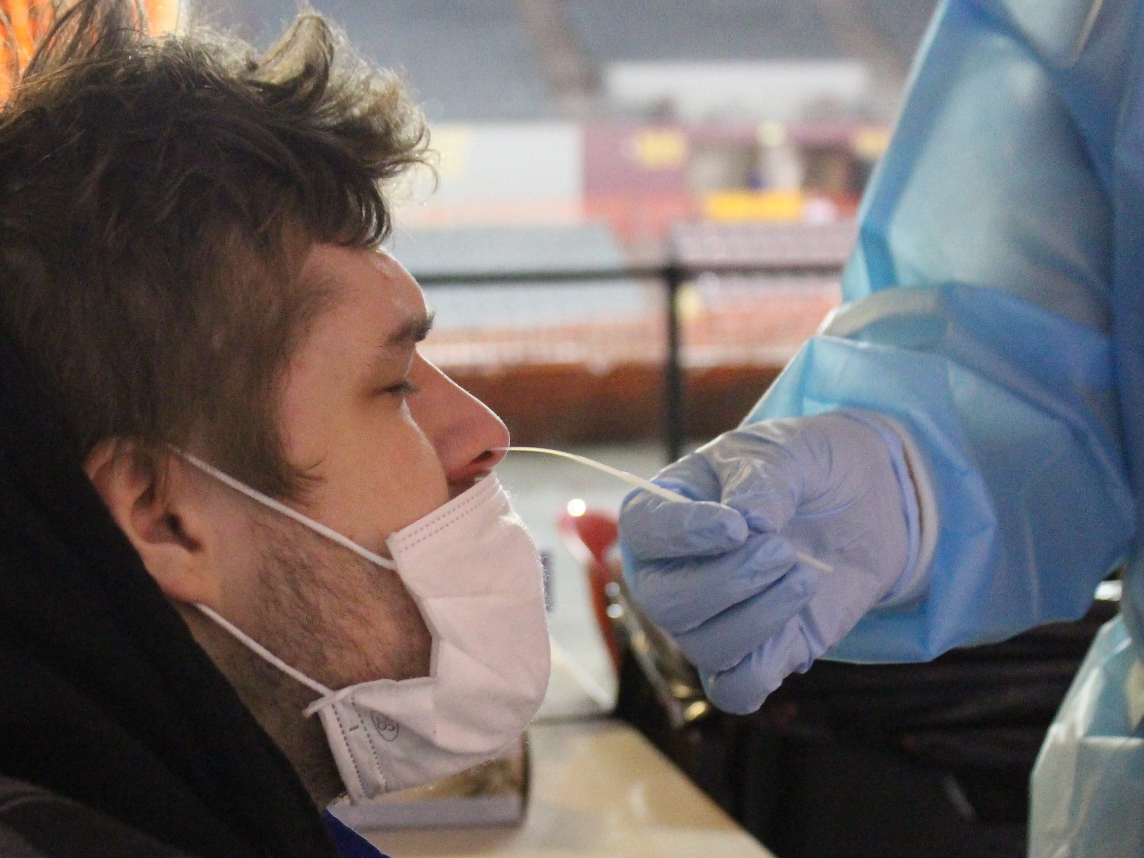 A white man gets his nose swabbed by a person in blue latex gloves
