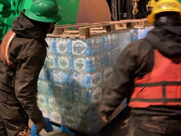 Workers load a pllete of water pbottles