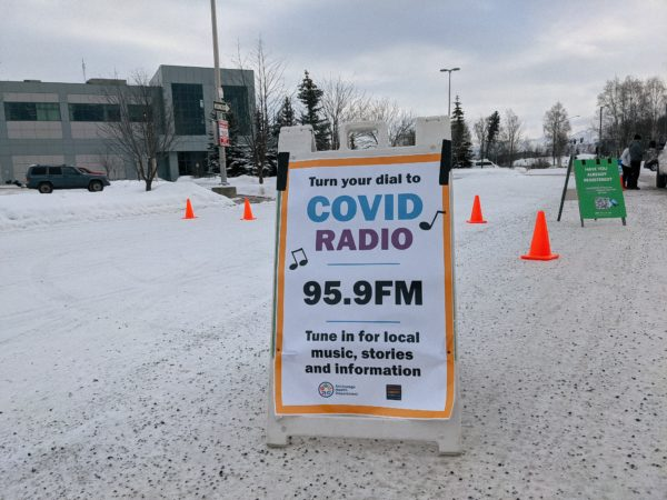 """A sign in a snowy parking lot reads """"COVID Radio 95.9 FM."""""""