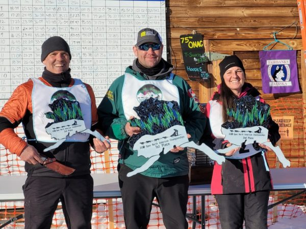 Three people in winter clothes stand in front of a buiulding wearing race bibs and alaska-shaped plaques