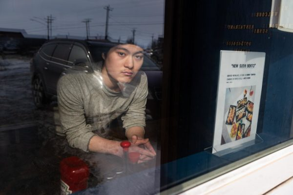 A young Korean man in a hooodie looks out the window of his restaurant