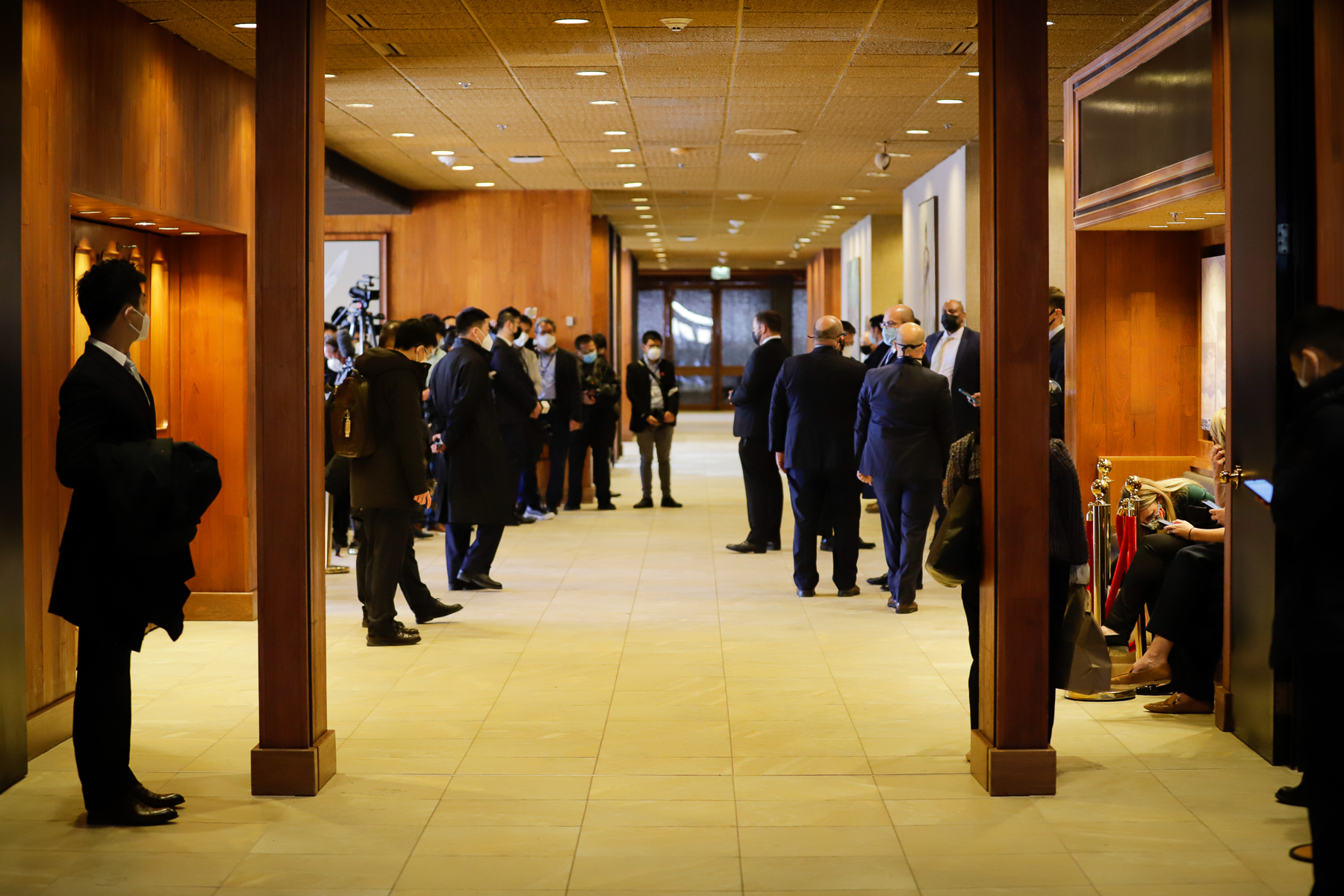 people withs masks on and mostly wearing suits in a hotel hallway
