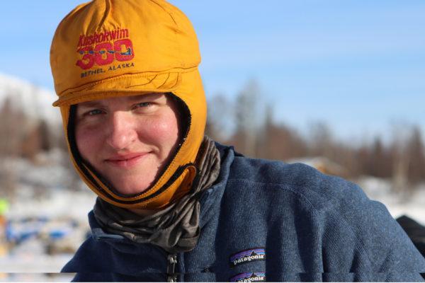 A woman smiles wearing a winter hat that says Kuskokwim 300 on it.