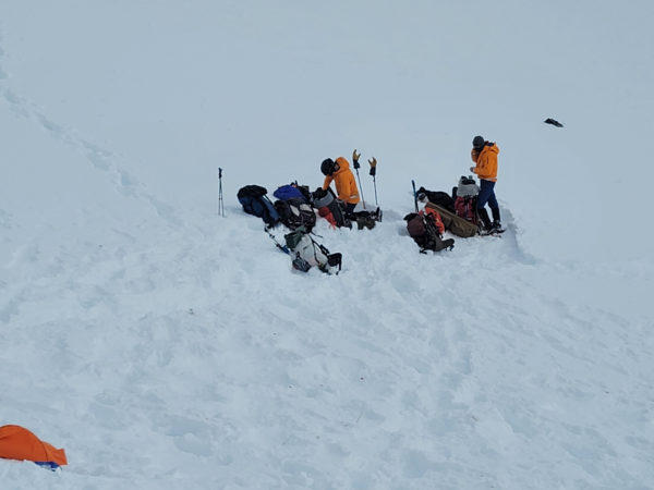 Two people with helicopters and sleds at a snowfield