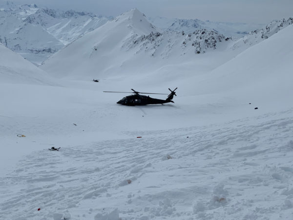A helicopter on a mountainaouus snow field