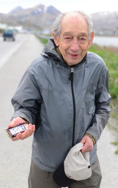 An old white man in a gray wind breaker holds a hershey bar