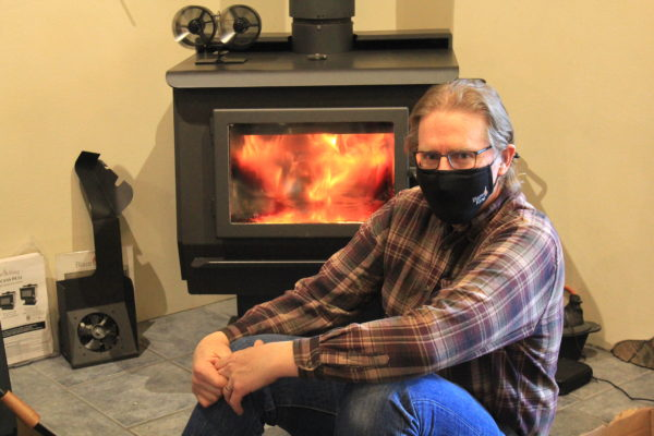 man sits in front of roaring woodstove
