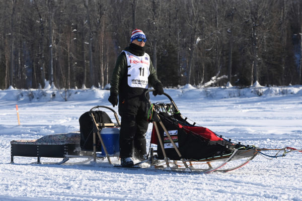 A musher on the back of a sled wearing a red-white-and blue hat.