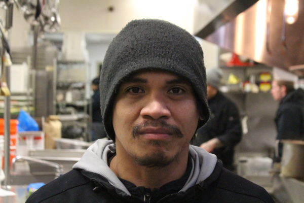 A filipino man wearing a beanie in front of a kitchen