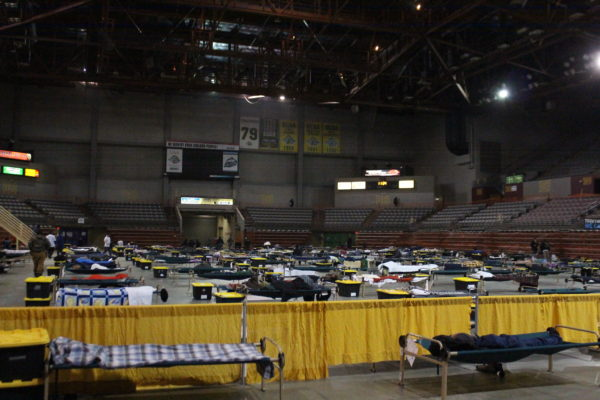 A floor of an arena with cots on the ground