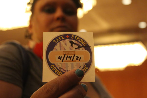 A person shows a sticker showing they got a first dose of the COVID-19 vaccine