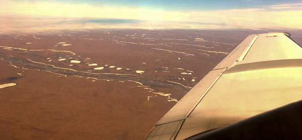 A flat area of land with rivers going through it as seen from an airplane