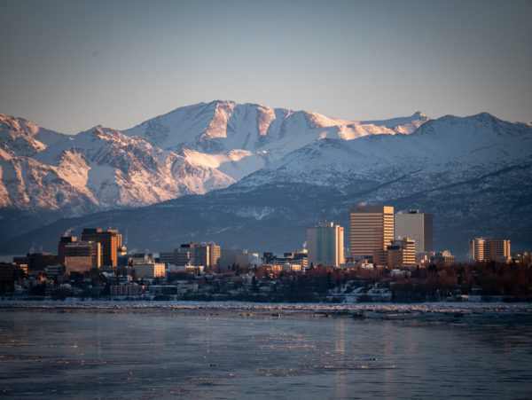 buildings stand in front of a snowy mountain range