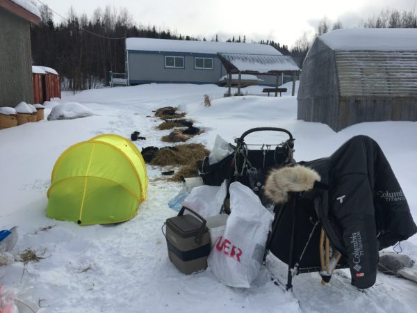 A yellow tent next to a sled in a snowy village.