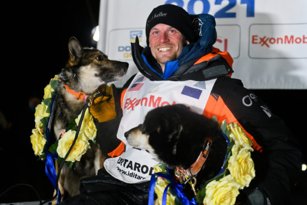 An Iditarod musher poses with two dogs wearing yellow flowers.