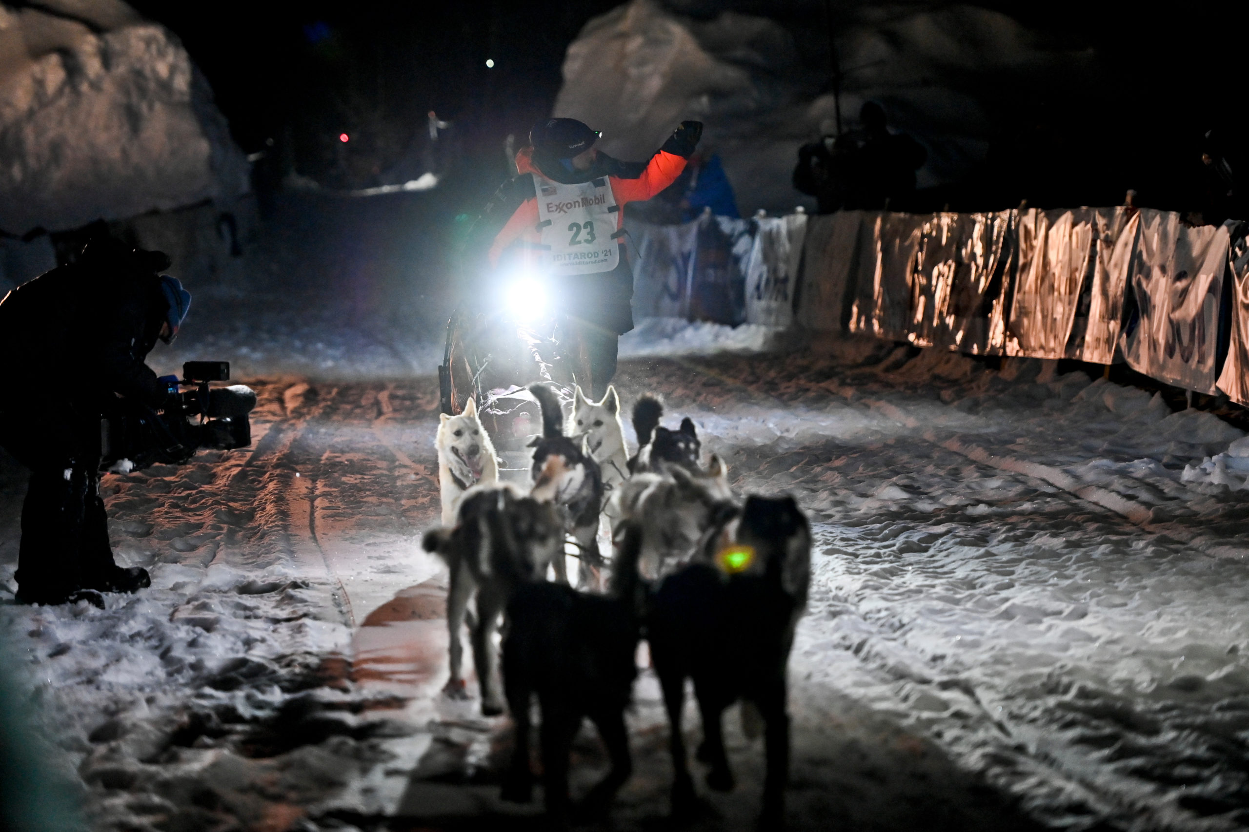 A dog musher and sled dogs race into a snowy finish line.