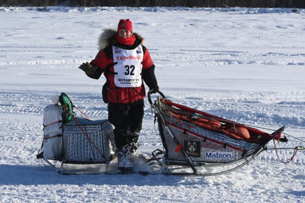 A musher waives to the crowd.