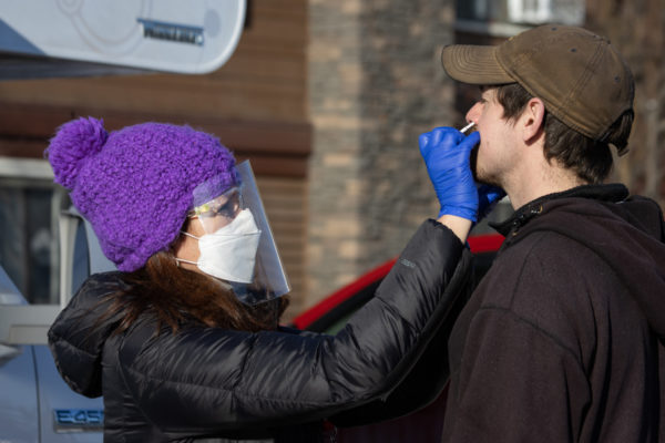 women in mask and face shield swabs inside a mans nostrils