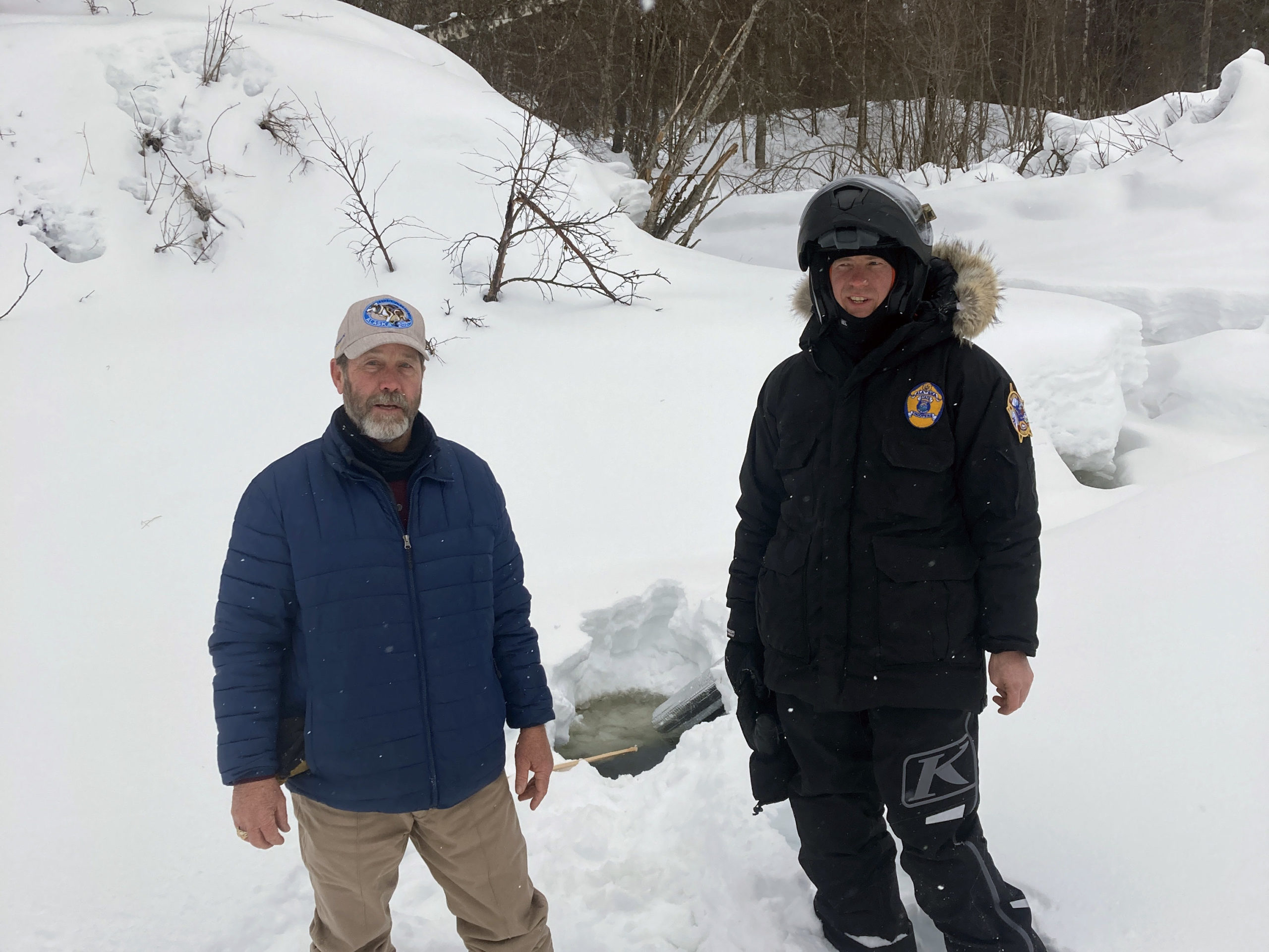 Two men in winter clothes stand in deep snow
