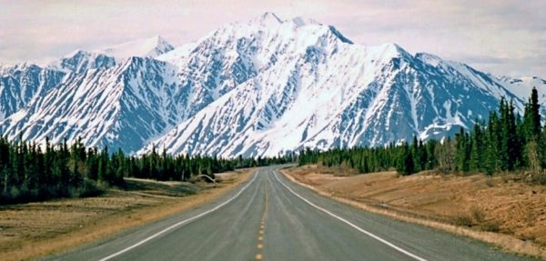 a two-lane road and big snow-covered mountains