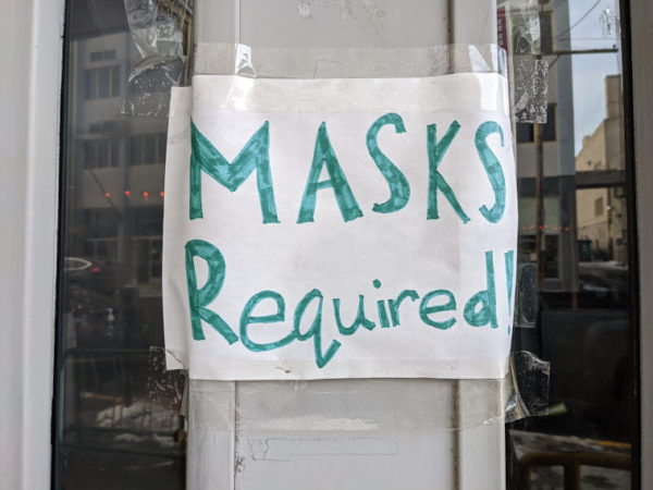 A hand-drawn sign at a downtown that says 'masks required'