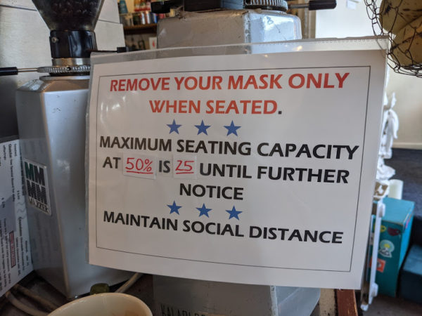 "A sign saying 'remove your mask only when seated, maximum seating capacity at 50% is 25 until further notice"" taped onto a coffee bean grinding machine"