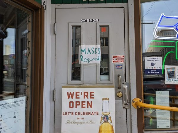 An entrance to a bar with 'masks required' written in