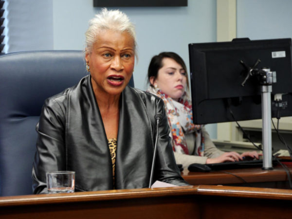 A black woan speaks at a podium