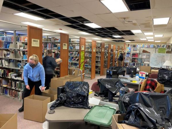 Wmen pack up books into boxes in front of rows of shelves of books