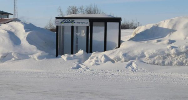 A bus stop halfway covered with snow