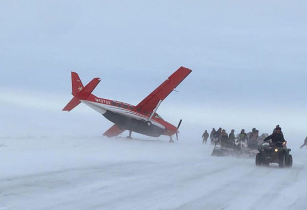 A plane in a blizzard leaning on one wing
