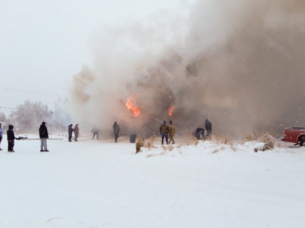 People gather in a snowy field as a smoke rises from a building