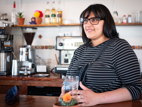 A person stands behind the counter at a coffee shop, holding a glass of water in their hands