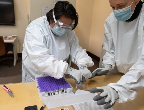 Two lab technicians wearing protective equipment transfer vials from a box.