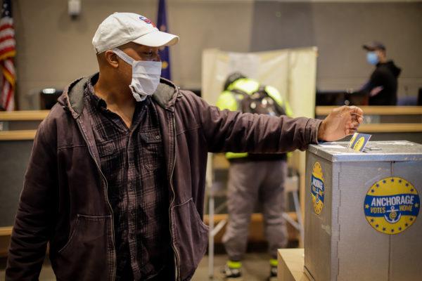 a person drops a ballot into a secure ballot box.