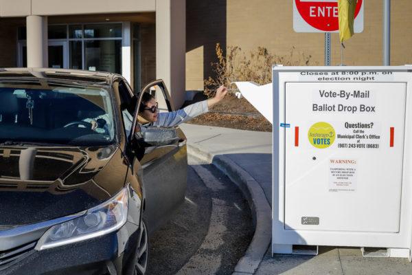 a person reaches out their car door to drop off a ballot in a secure ballot box.