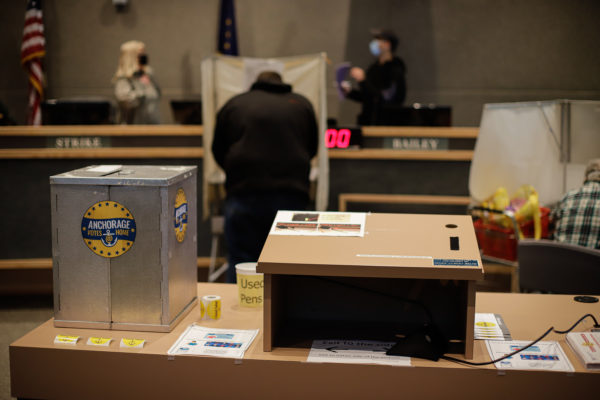 a ballot drop box sits on a table next to a podium. two people are in voting booths. two people are standing in the background