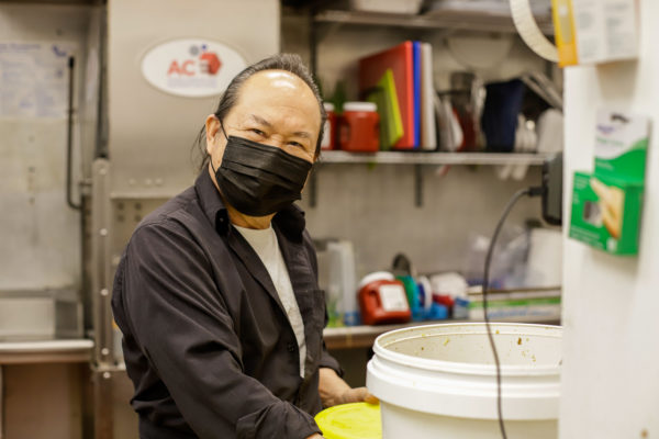 a restaurant employee looks toward the camera while holding a bowl