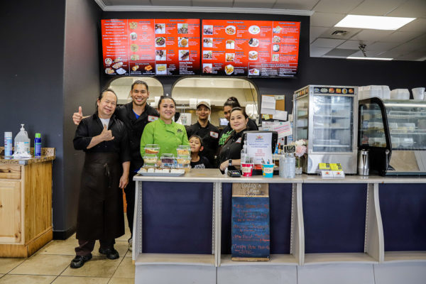 7 people pose for a group photo at a restaurant counter
