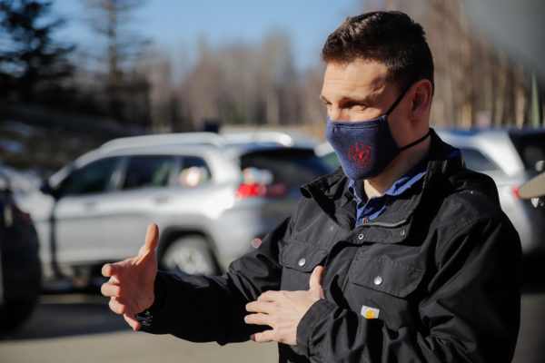 a person with a mask on speaks in a parking lot