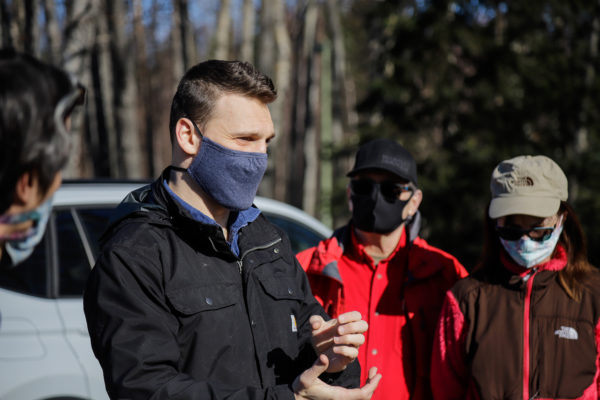 a person with a mask on talks with other people with masks on in a parking lot