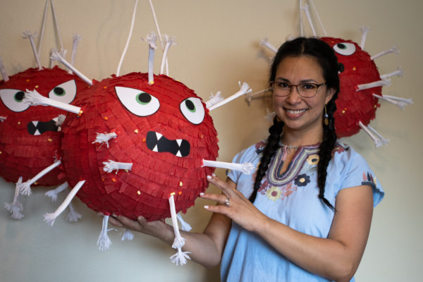 a woman smiling and standing between several COVID-19 piñatas