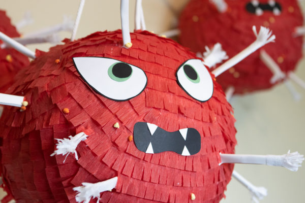 a red piñata with eyes and a mouth made to look like the COVID virus